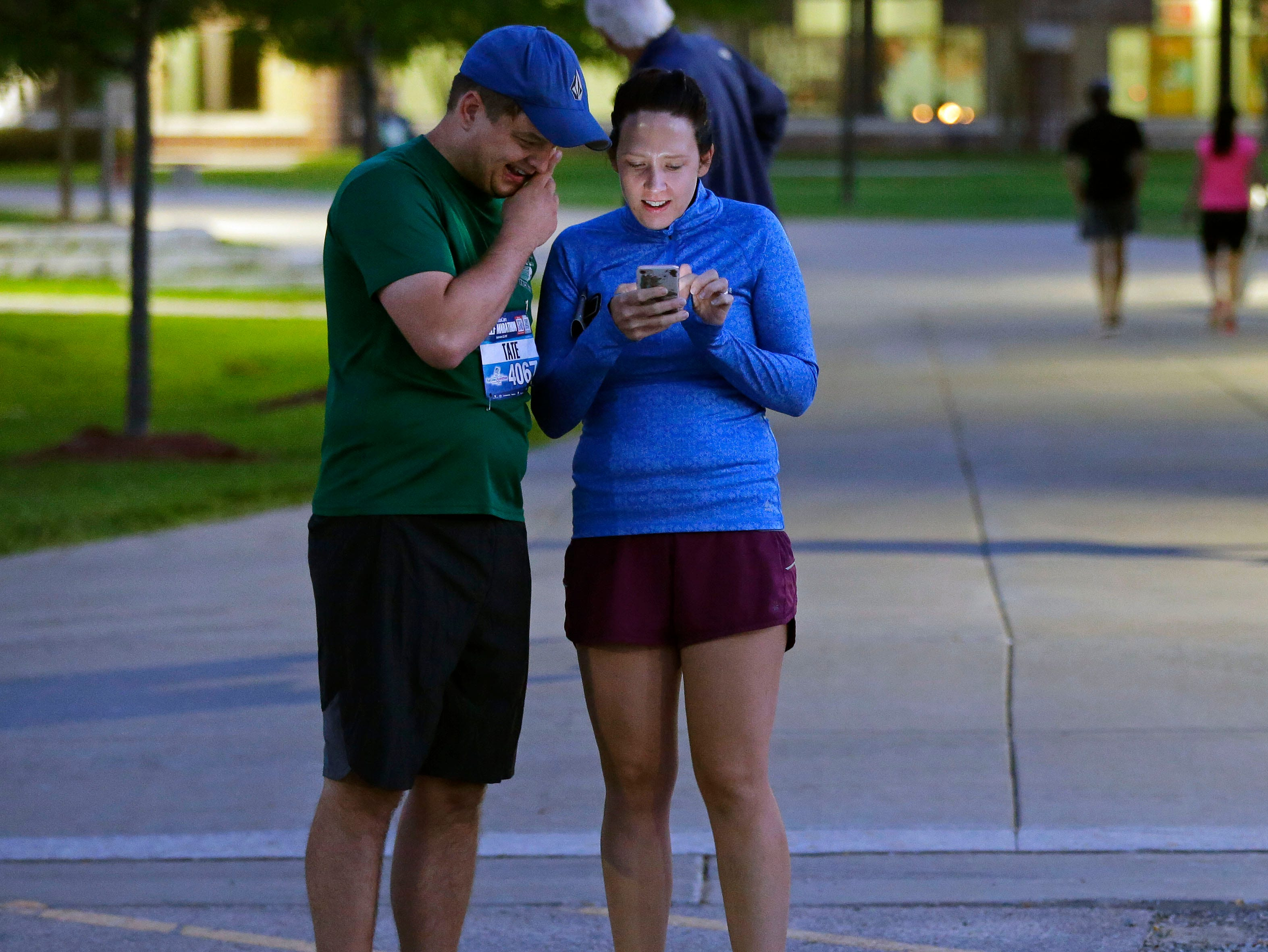 Tate and Courtney Plath send photos of how they are dressed so friends can spot them at the finish as the Community First Fox Cities Marathon takes place Sunday, September 23, 2018, across the Fox Cities.Ron Page/USA TODAY NETWORK-Wisconsin