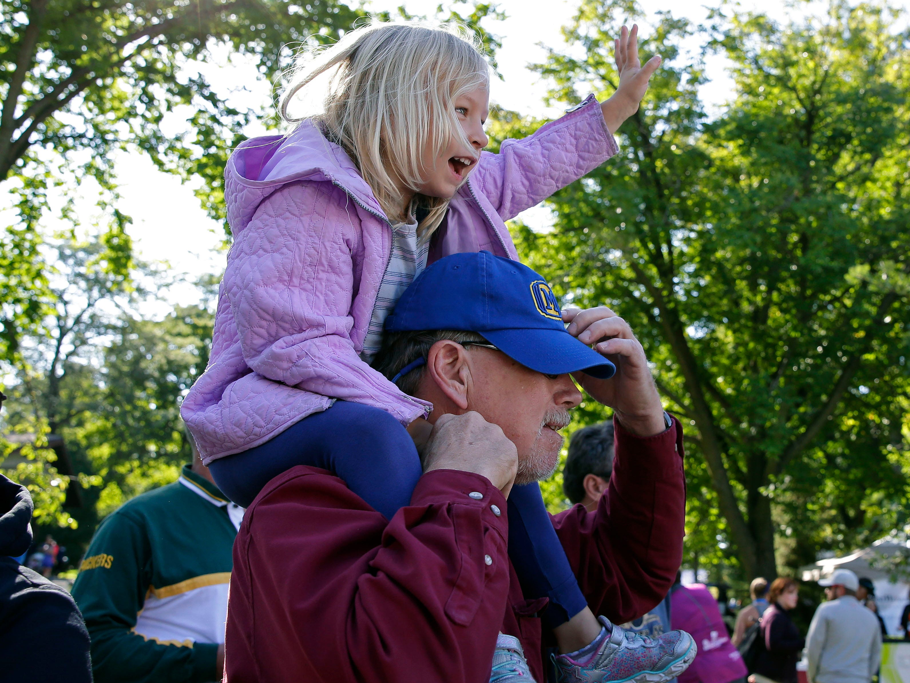 Regan Botzet sits on the shoulders of her grandfather, David Truyman, as she waves to her mother, Renee, at the finish of the Community First Fox Cities Marathon Sept. 23, 2018, across the Fox Cities.