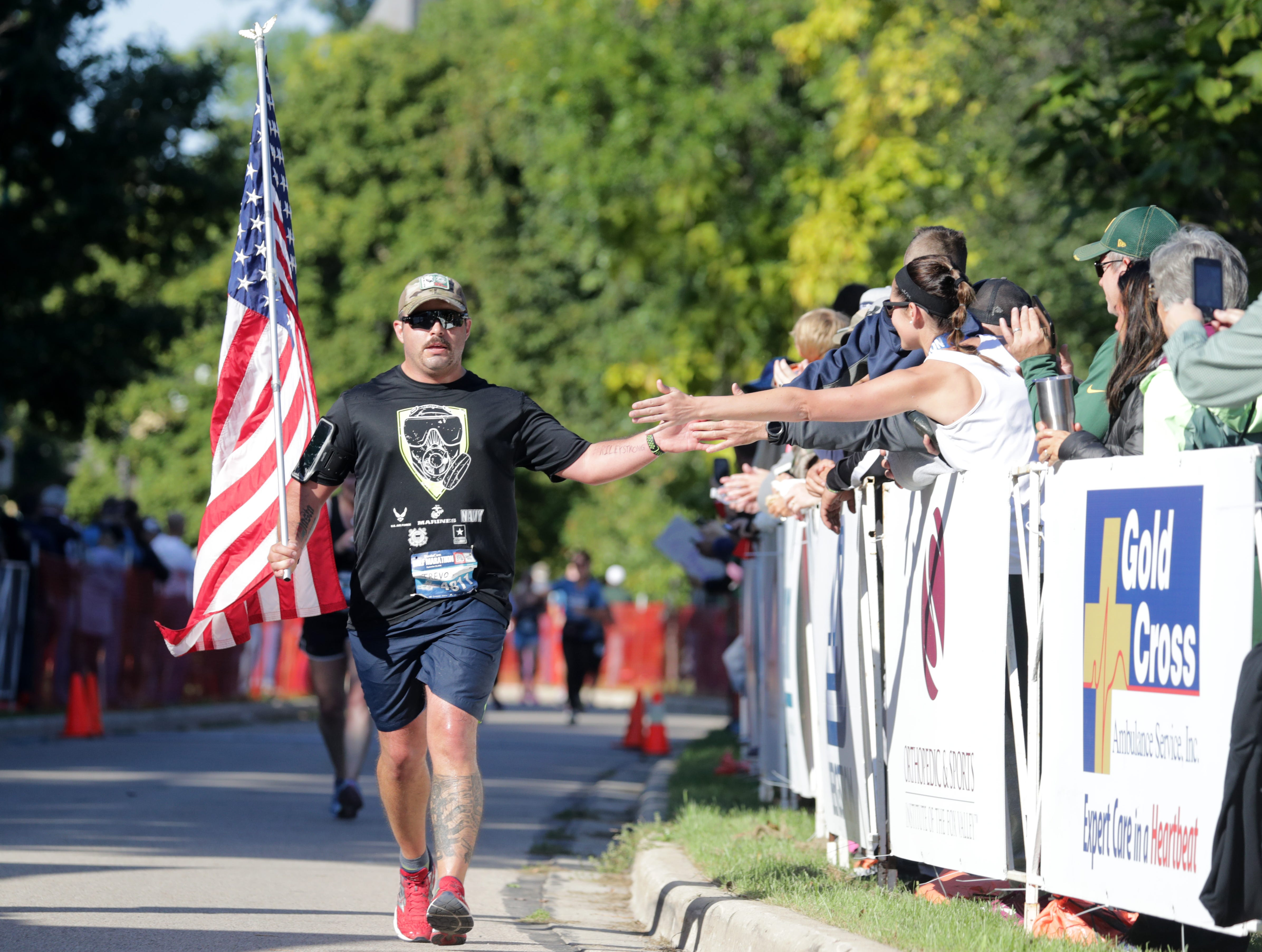 Trevor Anderson crosses the finish line in the half marathon event during the 28th annual Community First Fox Cities Marathon on Sept. 23, 2018, in Neenah, Wis.