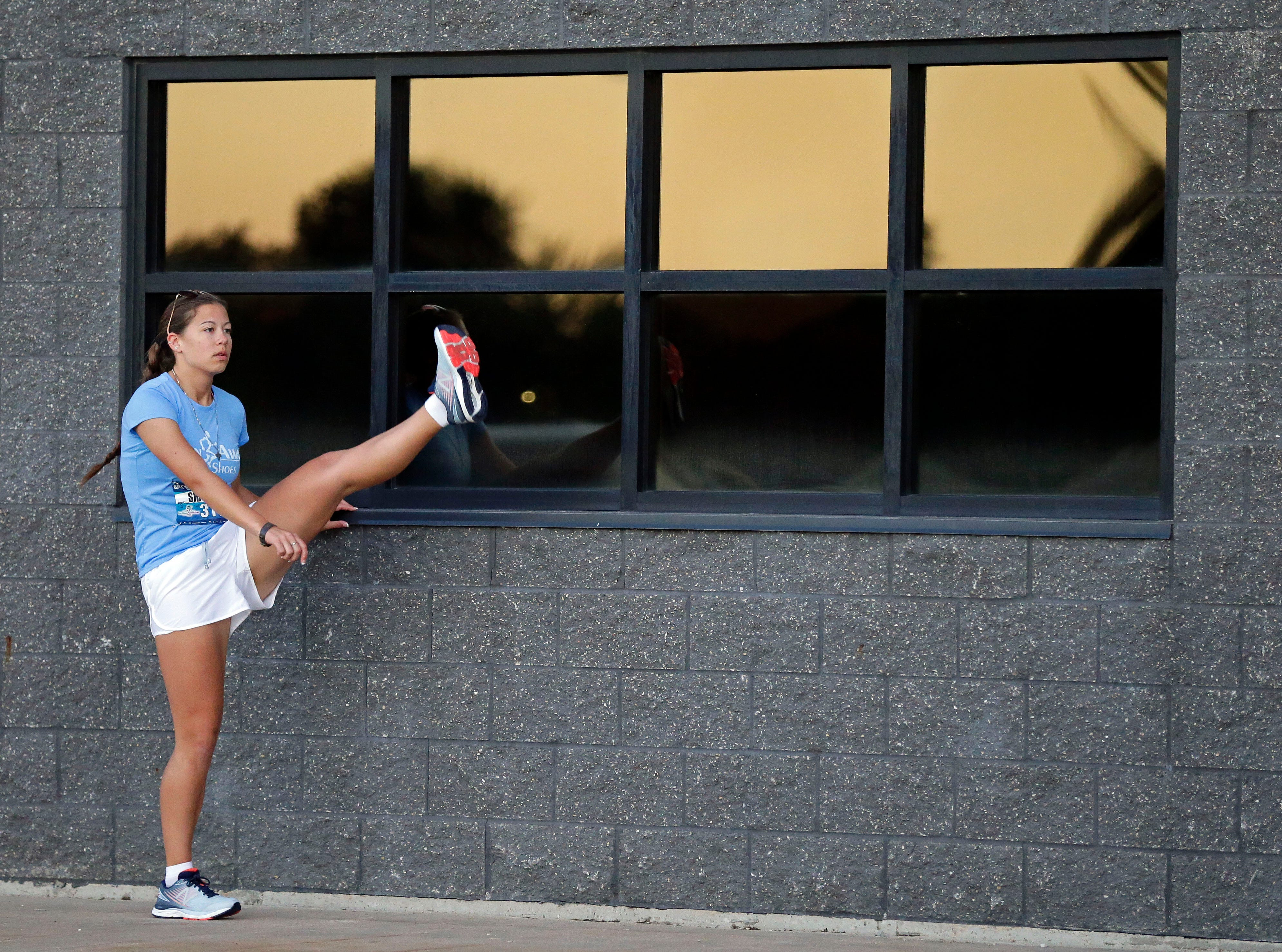 Shaylah Buss stretches before the Community First Fox Cities Marathon takes place Sunday, September 23, 2018, across the Fox Cities.