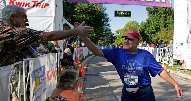 William Fahrenkrug gets congratulations at the finish of the Community First Fox Cities Marathon presented by Miron Construction on Sunday.