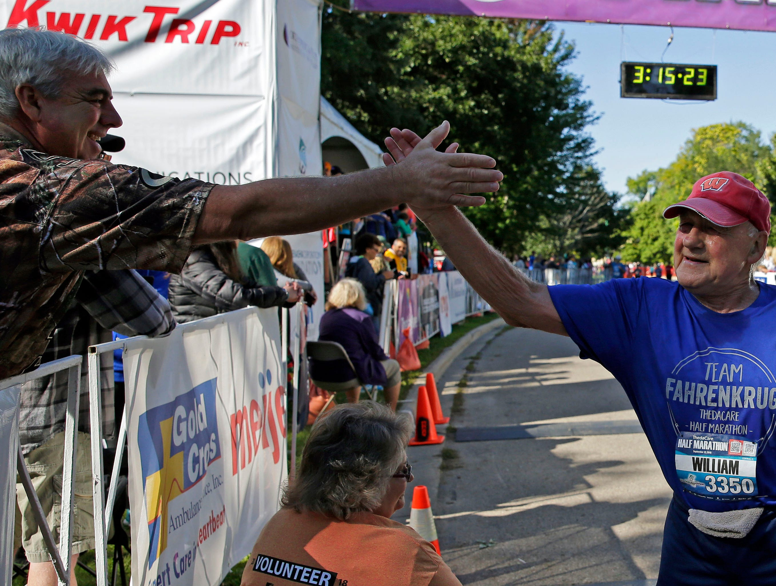 William Fahrenkrug gets congratulations at the finish as the Community First Fox Cities Marathon takes place Sept. 23, 2018, across the Fox Cities.
