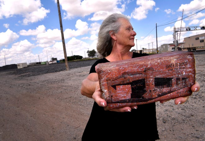 Paula Hatfield holds one of the commemorative bricks depicting the former Santa Fe Railroad depot in Snyder Wednesday Sept. 19, 2018. Hatfield is the vice chair of the Scurry County Historical Commission, she led a nearly ten-year effort to save the building which until a year ago stood behind her.