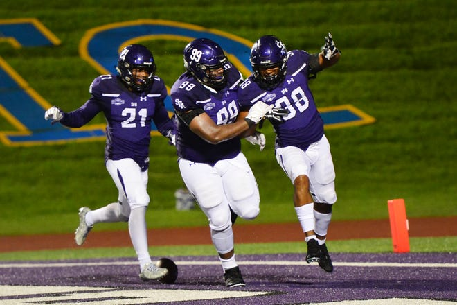 Stephen F. Austin's Trenton Gordon (38) celebrates with Shaq Henderson (99) and Davelle Fox (21) after recovering an ACU fumble in the end zone for a 17-7 lead with 3:35 left in the third quarter. SFA won the Southland Conference game 24-21 on Saturday, Sept. 22, 2018 in Nacogdoches.