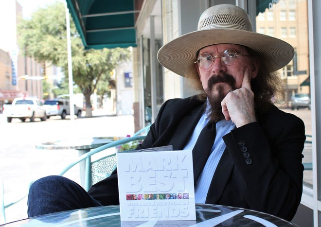 Mark Best, dapper in a straw hat over coat and tie, talks about his Beatles project at Monks Coffee Shop as the world passes by. Best formerly directed the Cooper orchestra.