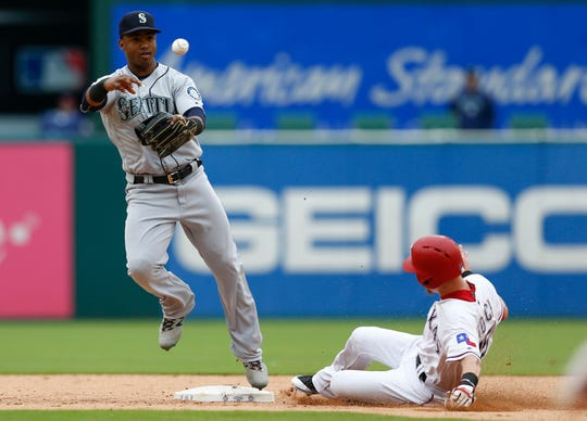 Seattle Mariners shortstop Jean Segura (left) throws to first base after forcing out Texas Rangers' Carlos Tocci to start a double play.