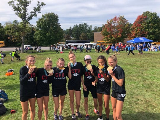 Members of the CVU girls cross-country running team bite their medals after winning the Large School division at the Manchester Invitational in New Hampshire on Saturday