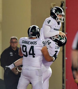 Michigan State Spartans kicker Matt Coghlin C.J. Hayes (4) jumps into the arms of quarterback Brian Lewerke (14) with tight end Chase Gianacakos (94) in celebration during the second half of the game against Indiana at Memorial Stadium.