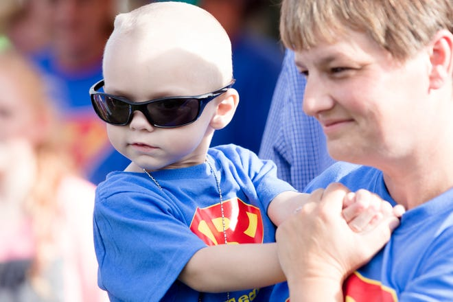 Brody Allen, held by his mother, Shilo, smiles while listening to Christmas carols during the Christmas Parade for Brody in Colerain Township on Sunday, Sept. 23, 2018. Brody has been diagnosed with terminal brain cancer.