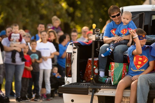 Shilo Allen holds her son Brody, the grand marshal, as he leads the Christmas Parade for Brody in Colerain Township on Sunday, Sept. 23, 2018. Brody has been diagnosed with terminal brain cancer.