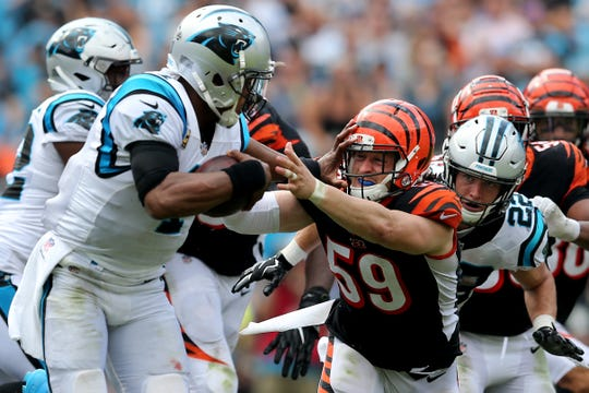 Cincinnati Bengals linebacker Nick Vigil (59) is stiff-armed by Carolina Panthers quarterback Cam Newton (1) in the fourth quarter during a Week 3 NFL game between the Cincinnati Bengals and the Carolina Panthers, Sunday, Sept. 23, 2018, at Bank of America Stadium in Charlotte, North Carolina. Carolina won 31-21.