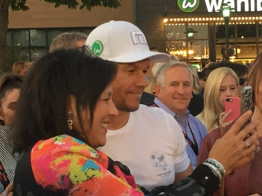 Actor Mark Wahlberg took selfies with people attending the grand opening of the Wahlburgers restaurant in West Des Moines.