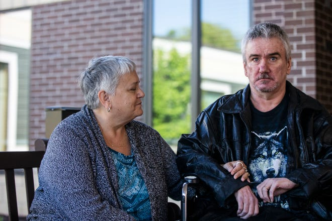 Linnea Clausen, of Craig near Sioux City, closes her eyes as she holds her husband, Gailen Clausen's arm on Sunday, Sept. 23, 2018, outside Bethany Life nursing home in Story City. Gailen has severe dementia from a condition called frontotemporal degeneration and Bethany Life, three hours from Craig, is the closest care facility that would accept Gailen.