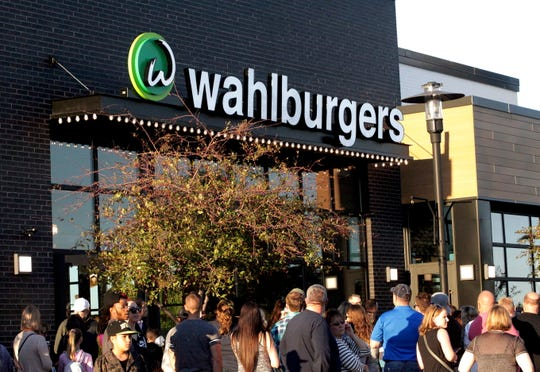 Hundreds of people attended the grand opening of a new Wahlburgers location in West Des Moines Saturday night.