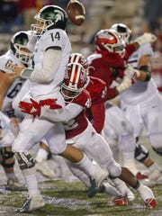 Brian Lewerke fumbles the ball while throwing, as Indiana's Marcelino Ball makes the hit.