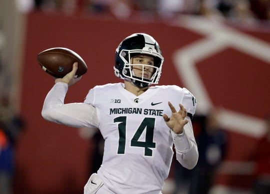 Brian Lewerke throws during the first half.