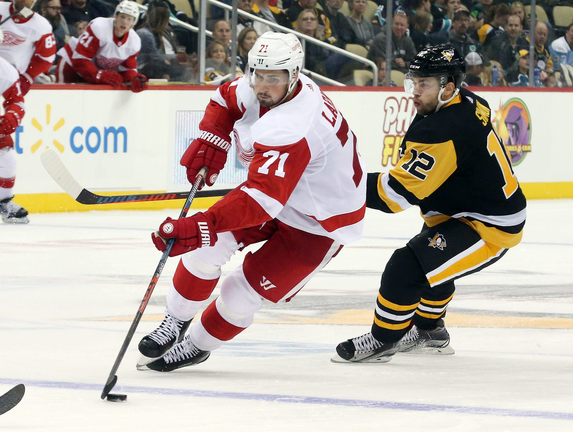 Red Wings center Dylan Larkin skates with the puck into the offensive zone ahead of Penguins center Dominik Simon during the third period of the Wings' 3-2 preseason win over the Penguins on Sunday, Sept. 23, 2018, in Pittsburgh.