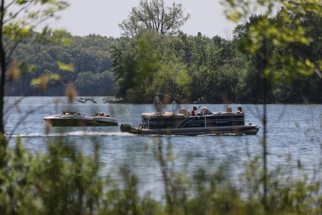 People enjoy the weather from their boats on Orchard Lake in Orchard Lake Village, Mich., on Friday, May 25, 2018.