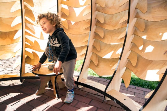 Asa Berkow-Pappas, 2 of Detroit checks out the sukkah by award-winning designer Noah Ives of Portland, Oregon for Sukkah x Detroit in Capitol Park in Detroit, Mich., Sunday, September 23, 2018.