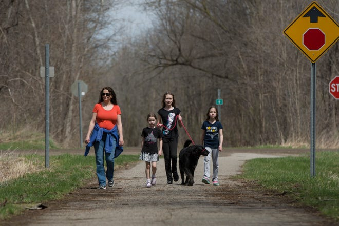 From left, Susie Hayes of New Hudson walks with her children Sophia, 6, Callie, 12, Claire, 9, and their dog Millie on the Huron Valley Trail in Lyon Township on April 10, 2017.