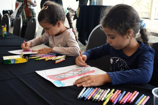 """Sisters Jowayreya, 5, left, and Taleen, 7, Garamoon of Sterling Heights add their own colors to drawings of the fresco details. People examine artist Hubert Massey's recently unveiled 30' x 30' fresco """"Detroit: Crossroad of Innovation"""" during a public celebration that included an artist talk and demonstrations at Cobo Center in Detroit on Sept. 23, 2018."""