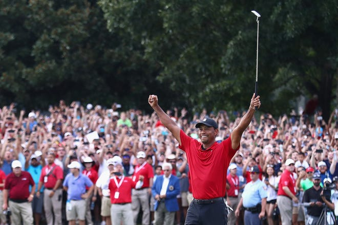 Tiger Woods celebrates making a par on the 18th green to win the Tour Championship at East Lake Golf Club in Atlanta on Sunday.
