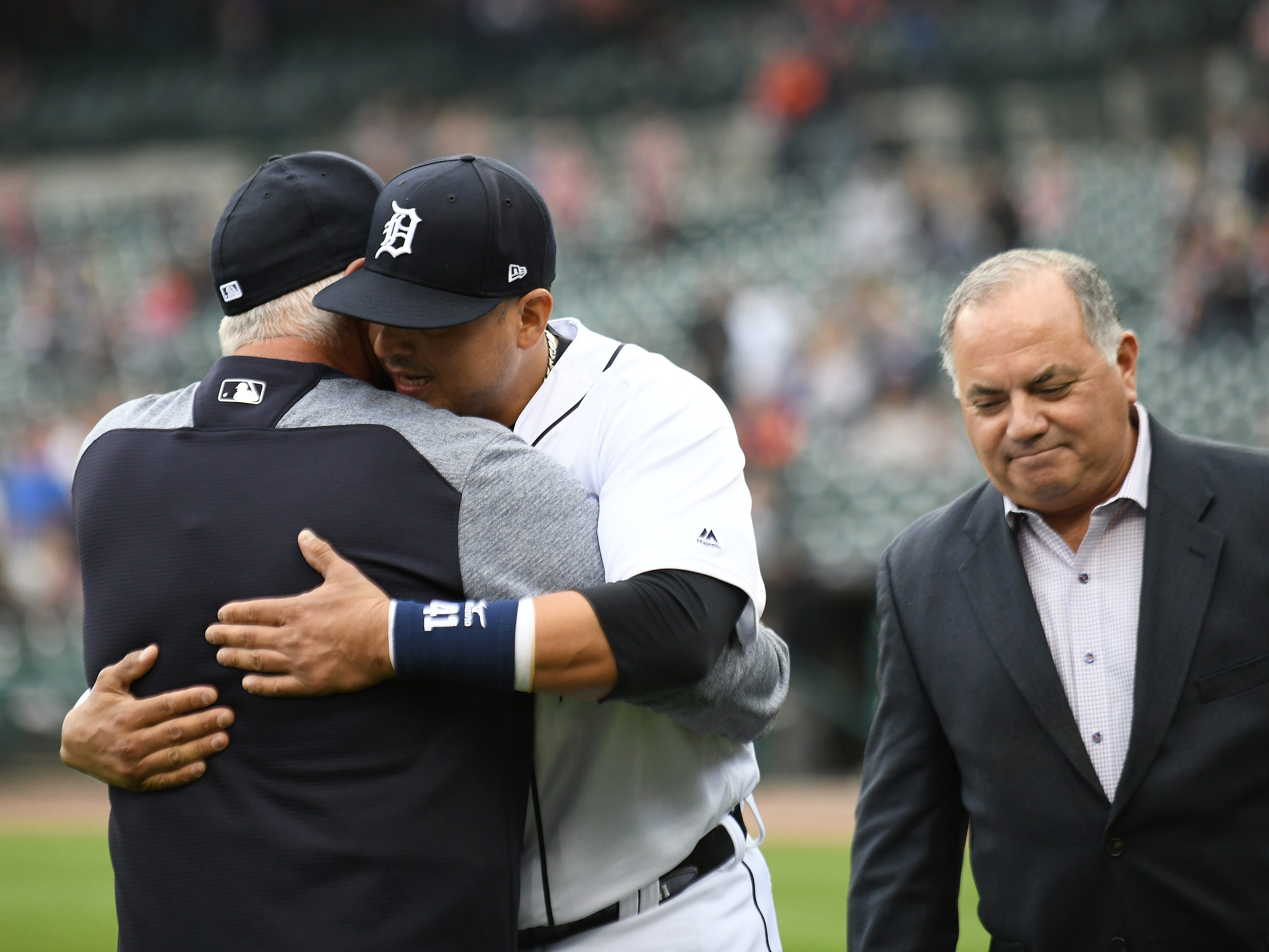 After hugging Al Avila, right, Victor Martinez hugs manager Ron Gardenhire during the ceremony.