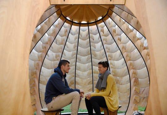 Noam Kimelman, 31, of Detroit and Jen Rusciano, 30, of Detroit sit inside the Seedling Sukkah.