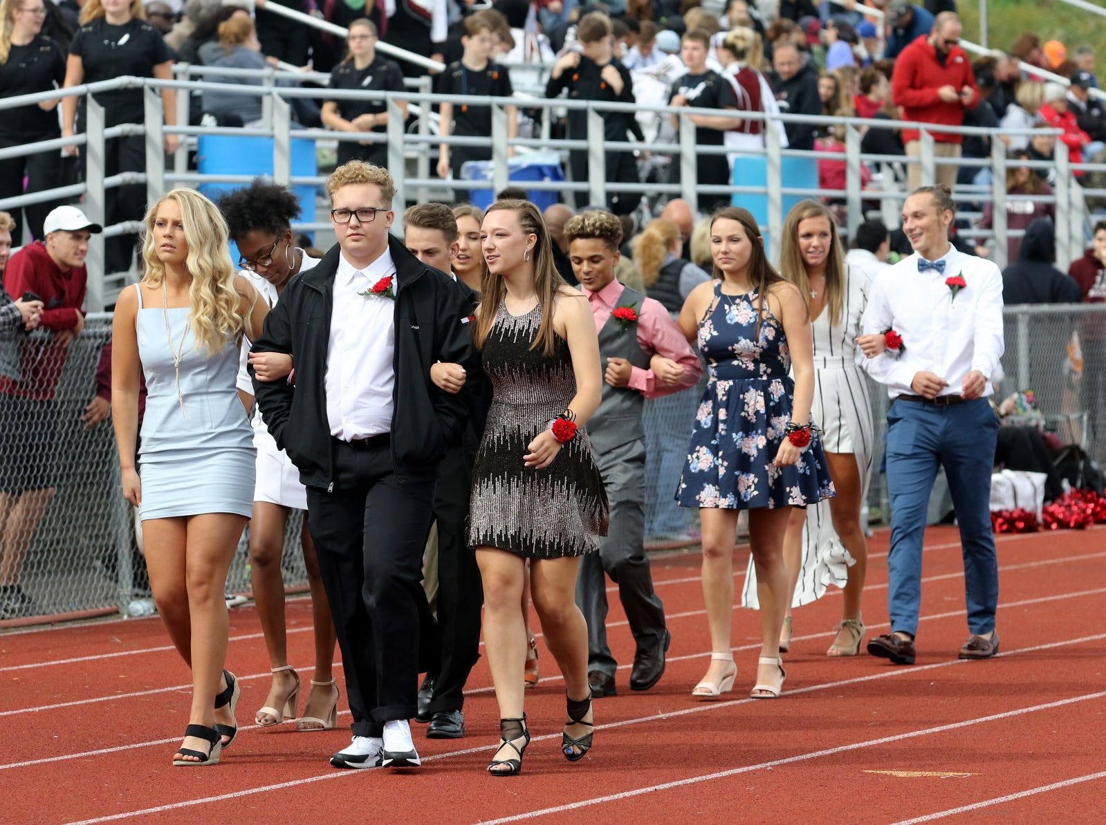 The Elmira High School homecoming court walks on the track at halftime of the football team's 30-8 victory over Syracuse Corcoran on Sept. 22, 2018 at Ernie Davis Academy.