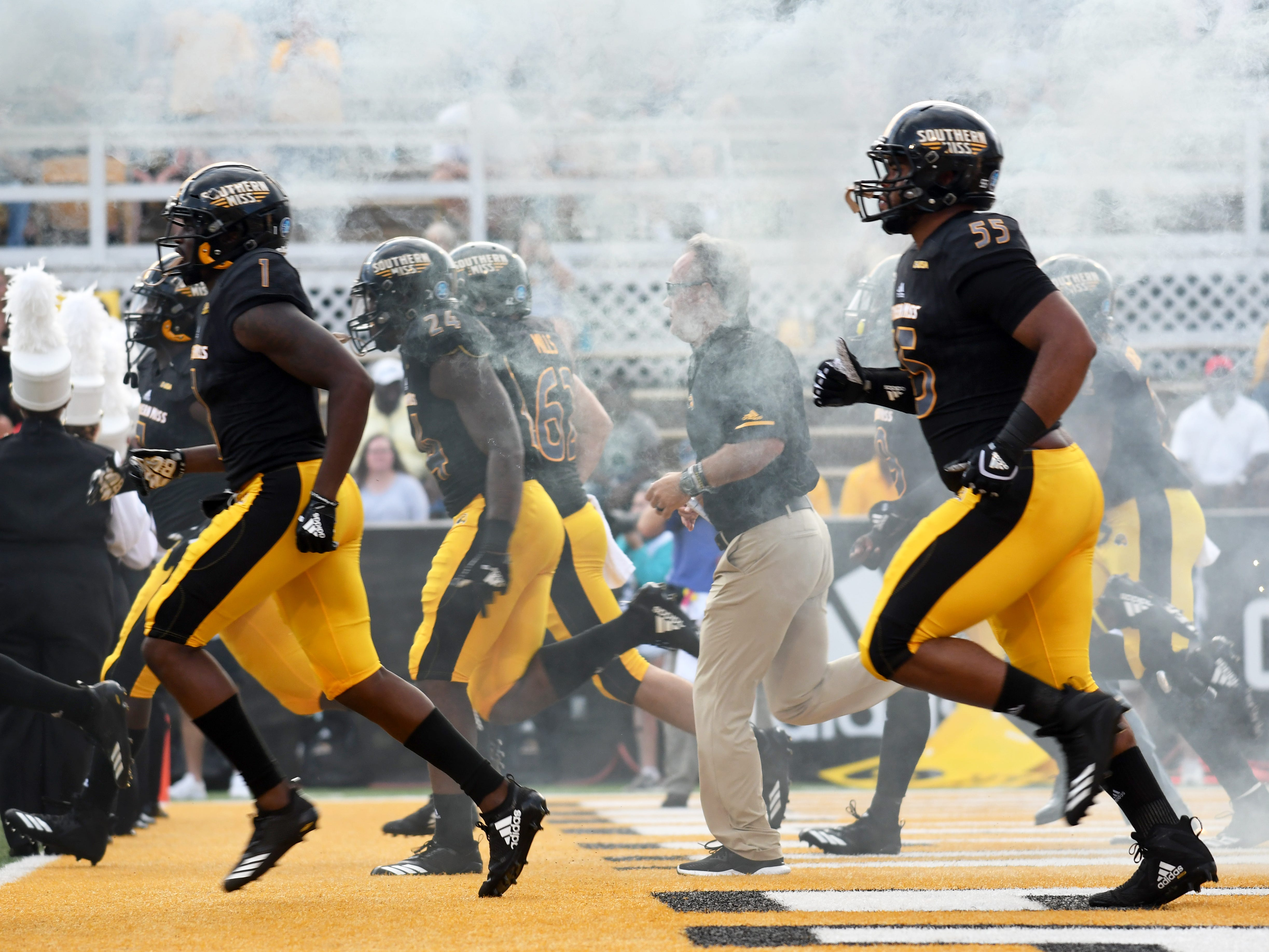 Southern Miss players and head coach Jay Hopson run onto the field at the start of a conference game against Rice at M.M. Roberts Stadium on Saturday, September 22, 2018.