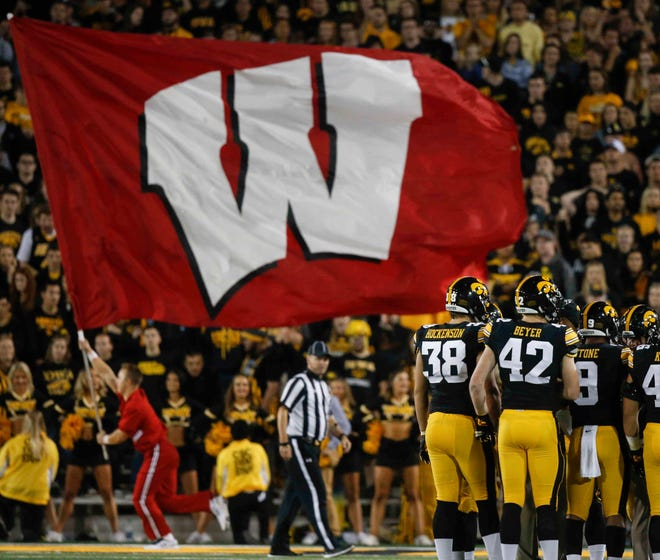 Members of the Iowa football team gather at the sideline as the Wisconsin flag is carried across the end zone after the Badgers scored late in the game to take the lead on Saturday, Sept. 22, 2018, at Kinnick Stadium in Iowa City.
