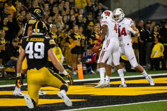 Wisconsin wide receiver A.J. Taylor (4) celebrates with Wisconsin tight end Jake Ferguson (84) after catching a touchdown pass in the fourth quarter during an NCAA football game on Saturday, Sept. 22, 2018, at Kinnick Stadium in Iowa City.