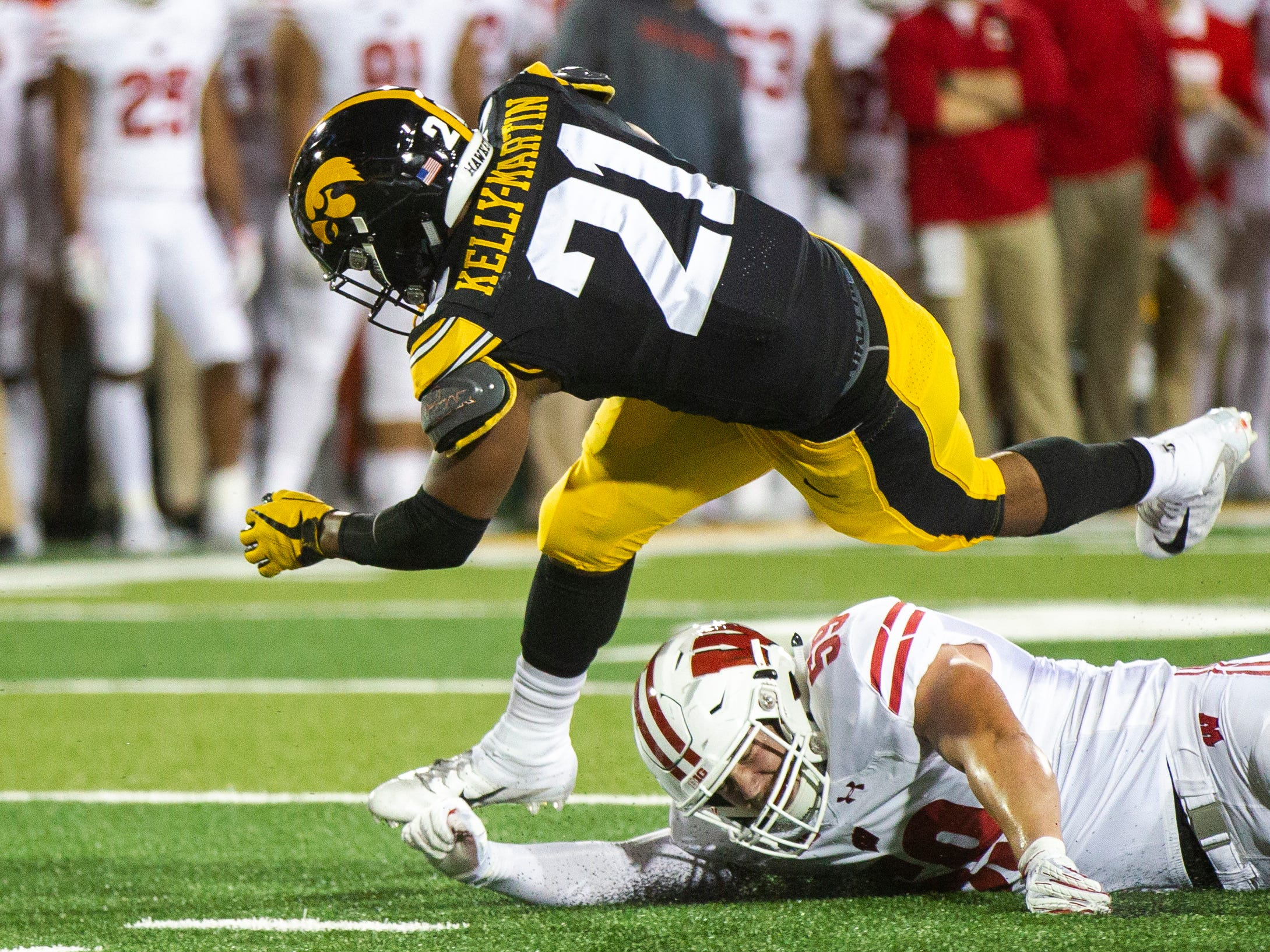Iowa running back Ivory Kelly-Martin (21) gets tripped up by Wisconsin linebacker Tyler Johnson (59) during an NCAA football game on Saturday, Sept. 22, 2018, at Kinnick Stadium in Iowa City.