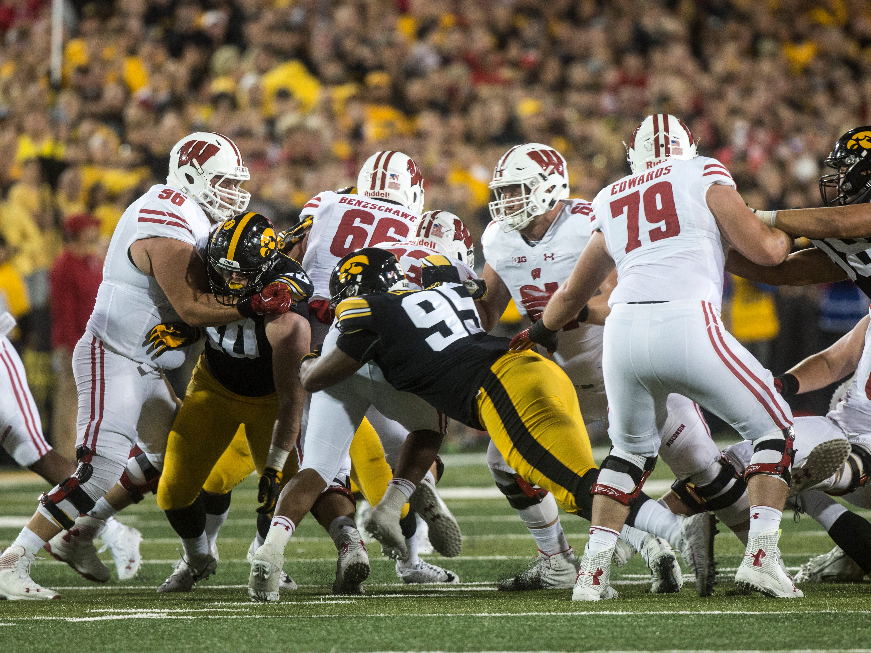 Iowa defensive lineman Cedrick Lattimore (95) tackles Wisconsin running back Jonathan Taylor (23) during an NCAA football game on Saturday, Sept. 22, 2018, at Kinnick Stadium in Iowa City.