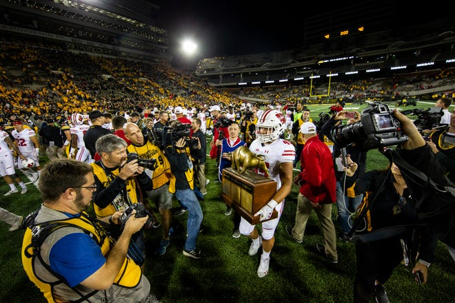 Wisconsin fullback Alec Ingold removes the Heartland Trophy from Kinnick Stadium after the Badgers' 28-17 win Saturday night.