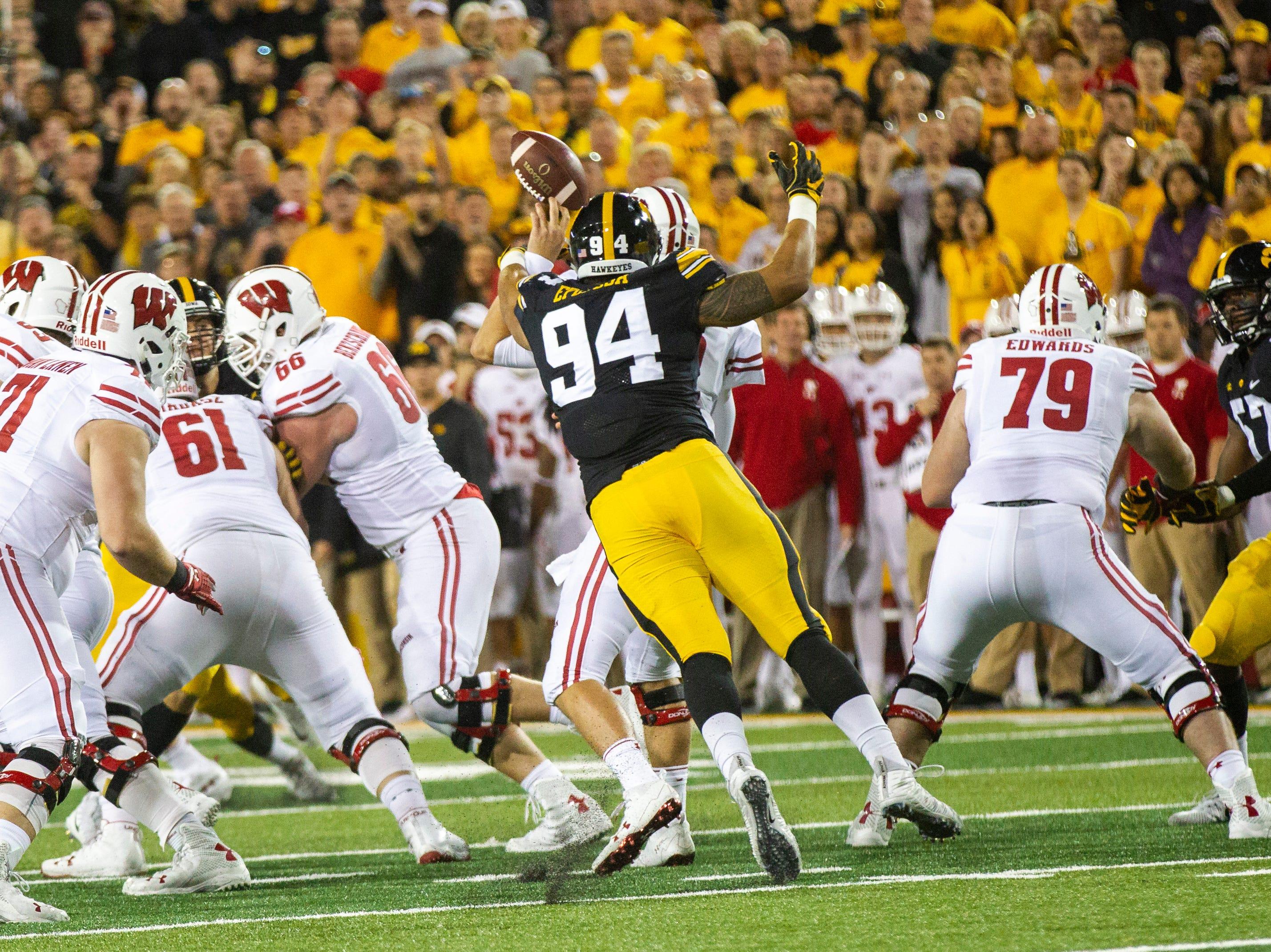 Iowa defensive end A.J. Epenesa (94) sacks Wisconsin quarterback Alex Hornibrook (12) during an NCAA football game on Saturday, Sept. 22, 2018, at Kinnick Stadium in Iowa City.