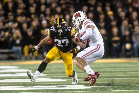 Iowa defensive back Amani Hooker (27) tackles Wisconsin wide receiver Danny Davis III.