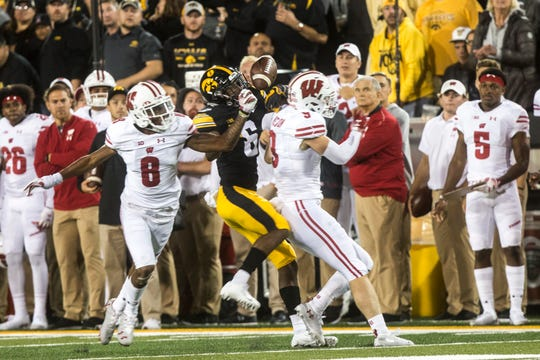 Iowa wide receiver Ihmir Smith-Marsette (6) can't come up with a pass while being covered by Wisconsin cornerback Deron Harrell (8) and Wisconsin safety Scott Nelson (9) during an NCAA football game on Saturday, Sept. 22, 2018, at Kinnick Stadium in Iowa City.