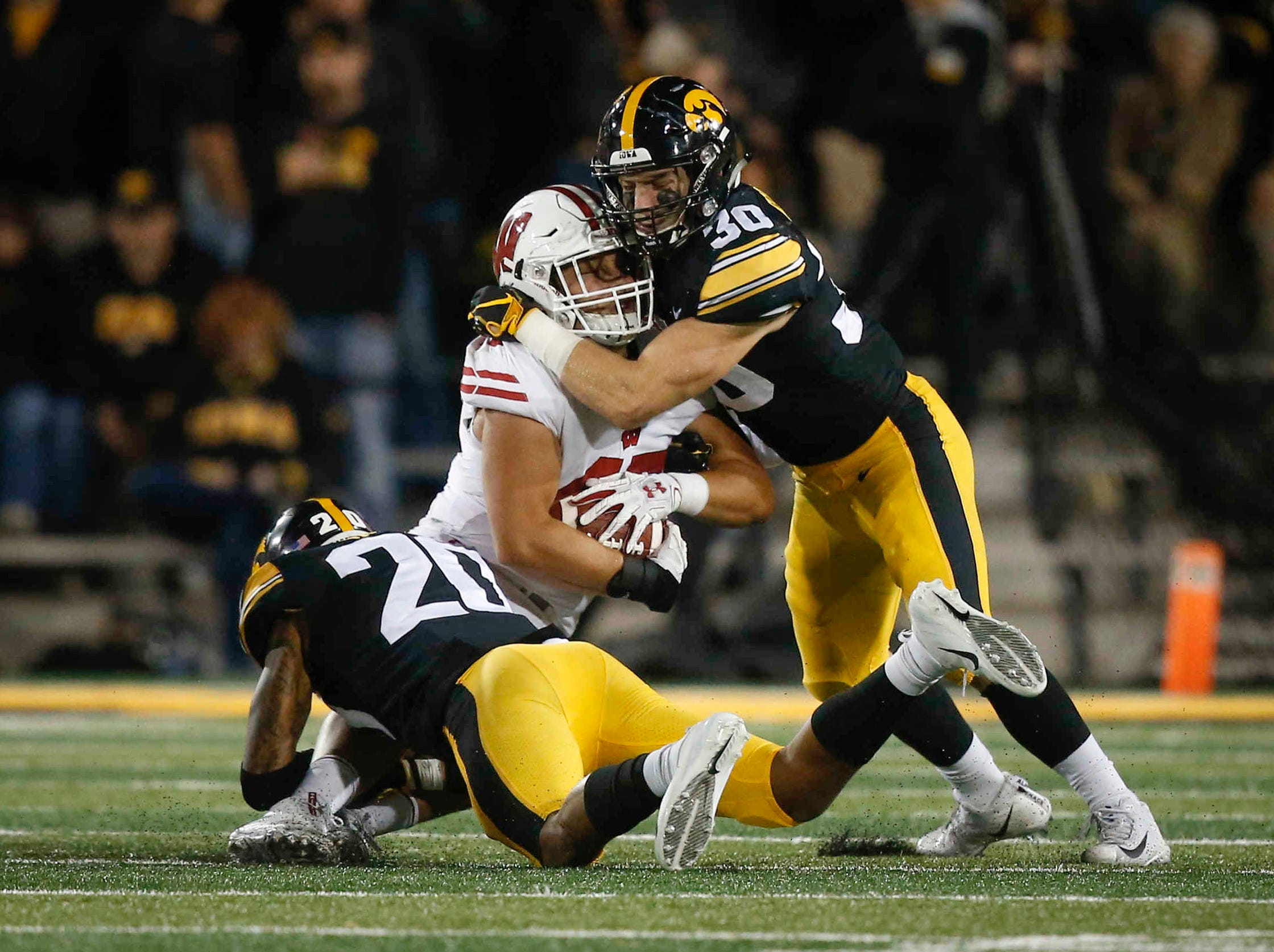 Iowa safety Jake Gervase, right, and cornerback Julius Brents team up to bring down a Wisconsin receiver on Saturday, Sept. 22, 2018, at Kinnick Stadium in Iowa City.