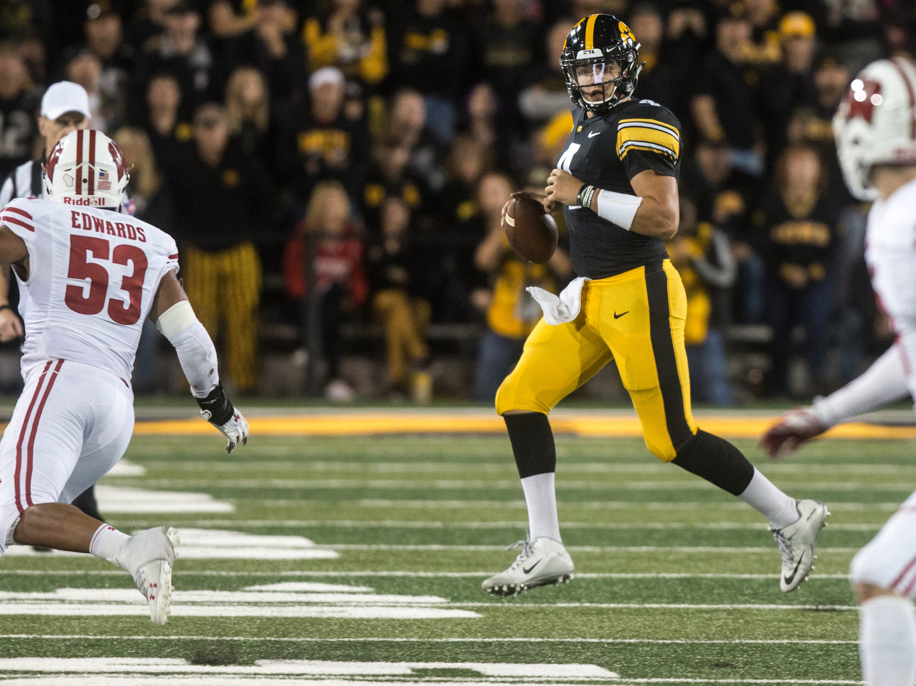 Iowa quarterback Nate Stanley (4) looks to pass while Wisconsin defenders close in during an NCAA football game on Saturday, Sept. 22, 2018, at Kinnick Stadium in Iowa City.