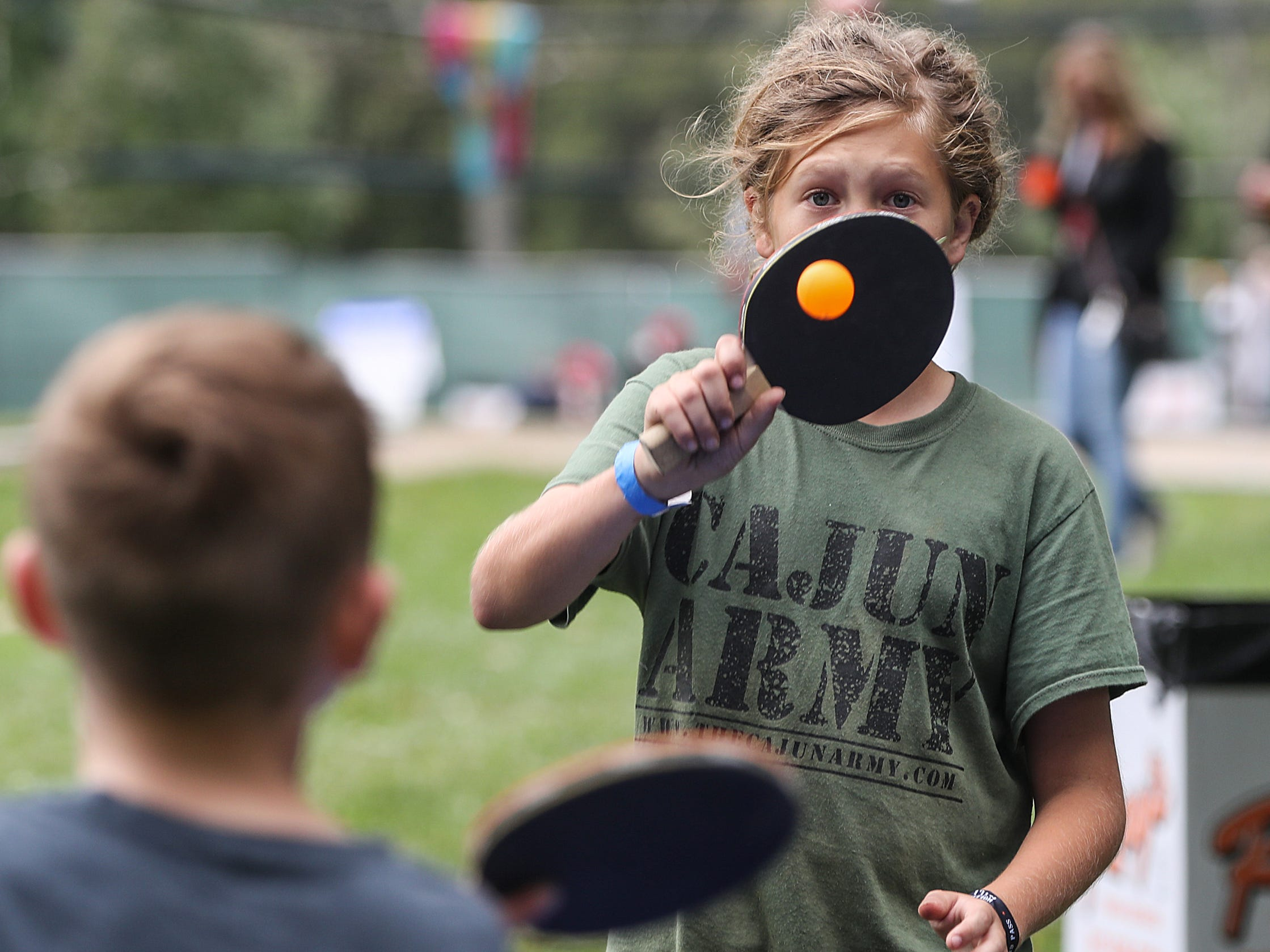Justus Cray, 12, plays ping pong with a friend during the inaugural Holler on the Hill music festival at Garfield Park in Indianapolis, Saturday, Sept. 22, 2018.