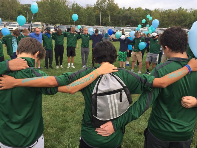 Members of the Zionsville Community High School boys tennis team lock arms during a prayer vigil at Lions Park in Zionsville to remember Harrison Hunn, 15, and Shelby Hunn, 13, who died earlier this week. Tennis team members wrote their names on their arms.