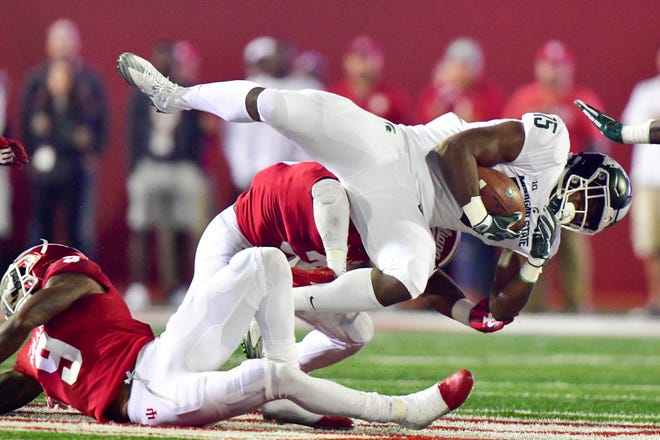 Sep 22, 2018; Bloomington, IN, USA;Michigan State Spartans running back La'Darius Jefferson (15) falls to the ground after being hit by Indiana Hoosiers defensive back Bryant Fitzgerald (31) during the first half of the game at Memorial Stadium . Mandatory Credit: Marc Lebryk-USA TODAY Sports