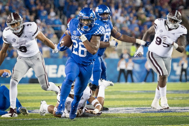 Kentucky running back Benny Snell Jr. (26) avoids the tackle of several Mississippi State and runs for a touchdown during the second half of an NCAA college football game in Lexington, Ky., Saturday, Sept. 22, 2018. (AP Photo/Bryan Woolston)