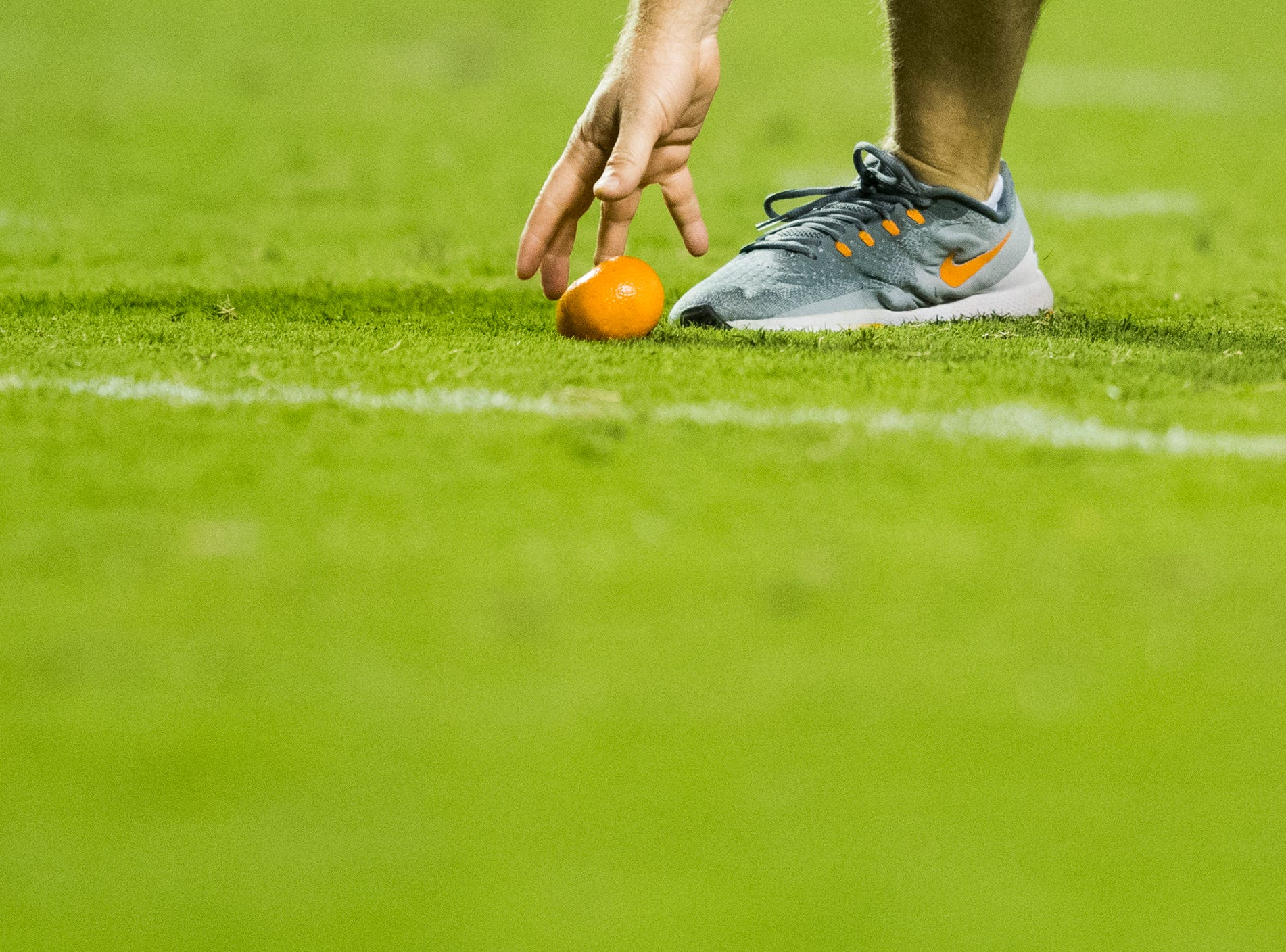 A staff member removes a tangerine that was thrown onto the playing field after a call against Tennessee during a game between Tennessee and Florida at Neyland Stadium in Knoxville, Tennessee on Saturday, September 22, 2018.