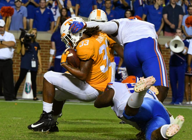 Tennessee running back Jeremy Banks (33) is tackled by two Florida defenders during second half of their 47-21  in Neyland Stadium Saturday, September 22, 2018 in Knoxville, Tenn.
