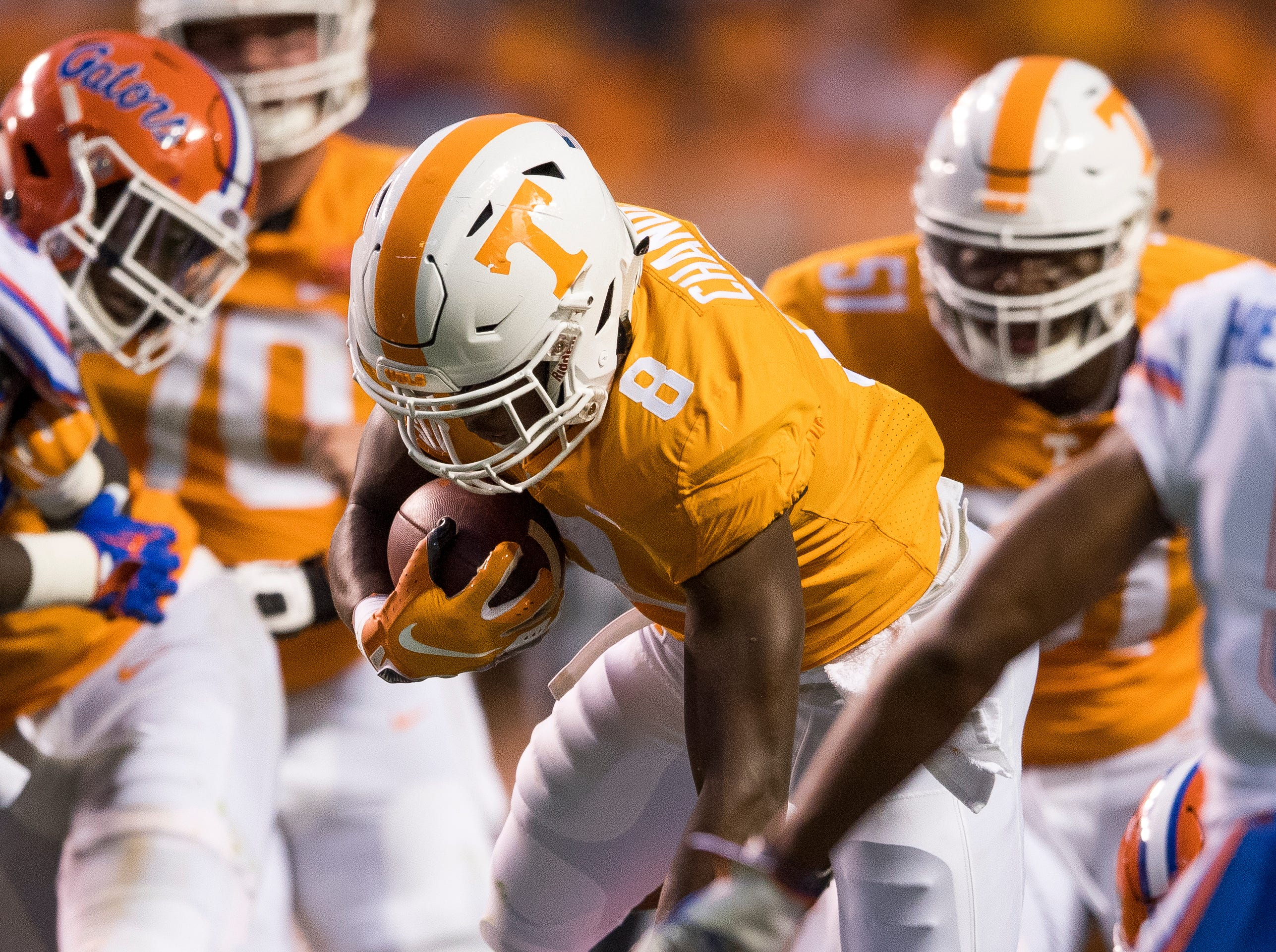 Tennessee running back Ty Chandler (8) leaps over Florida defensive back Brad Stewart, Jr. (2) during the Tennessee Volunteers' game against Florida in Neyland Stadium on Saturday, Sept. 22, 2018.