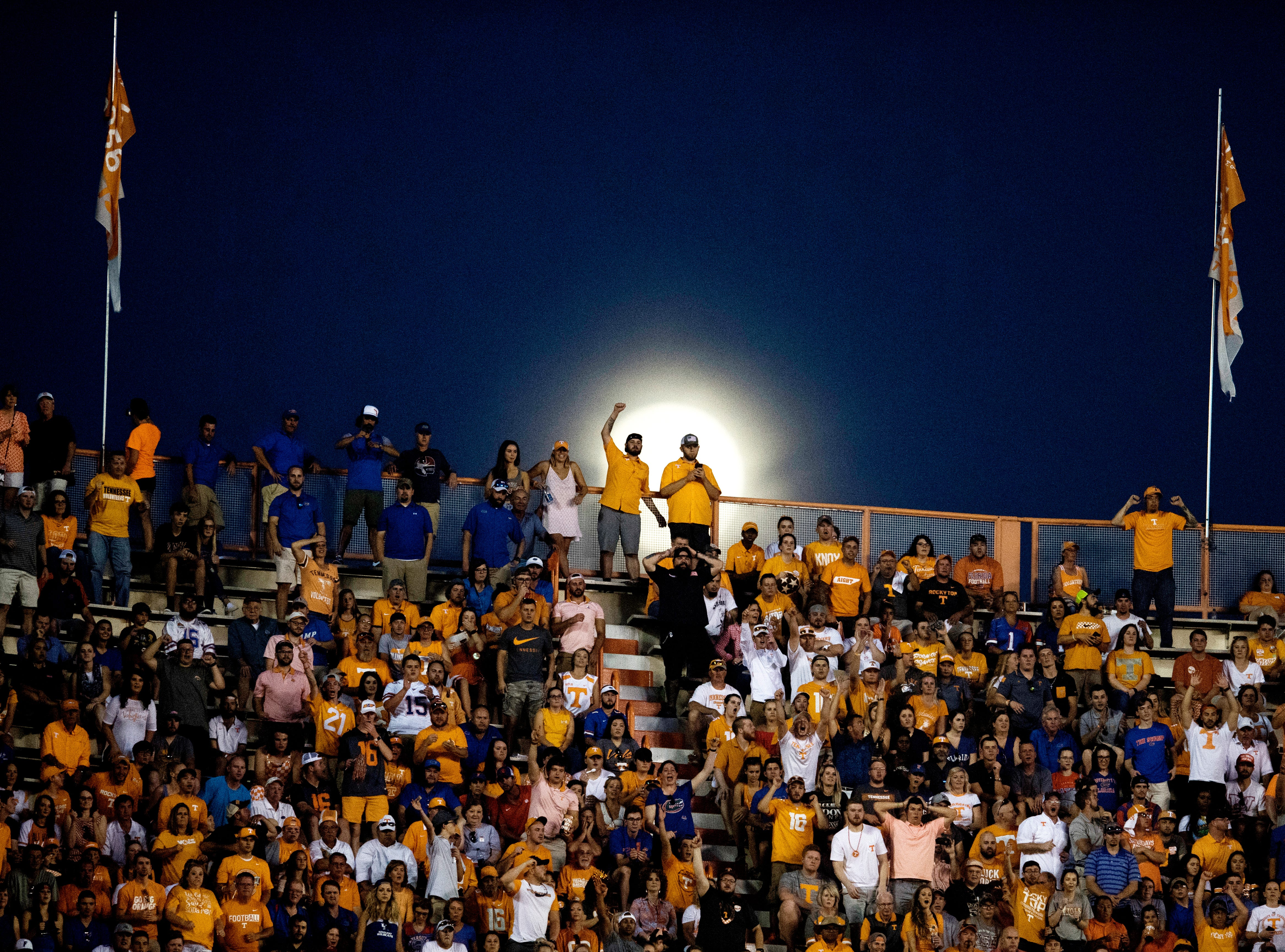 Fans cheer from the stands as the moon rises in the distance during a game between Tennessee and Florida at Neyland Stadium in Knoxville, Tennessee on Saturday, September 22, 2018.