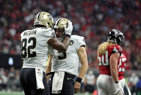 New Orleans Saints quarterback Drew Brees (9) celebrates his rushing touchdown with tight end Benjamin Watson (82) in the fourth quarter against the Atlanta Falcons Sunday at the Mercedes-Benz Stadium in Atlanta.