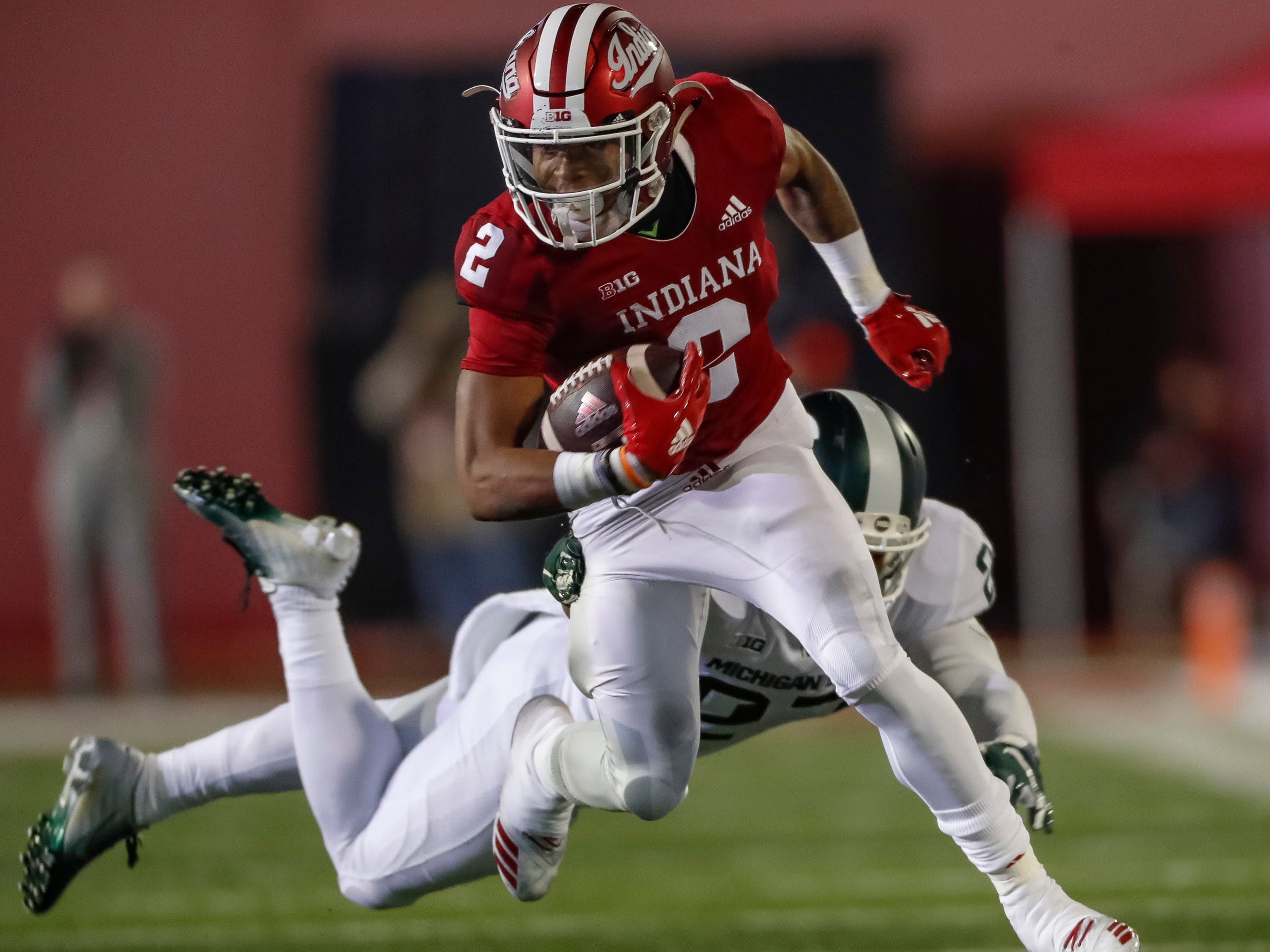 Reese Taylor #2 of the Indiana Hoosiers runs the ball as Khari Willis #27 of the Michigan State Spartans tries to make the stop from behind during the first half of action at Memorial Stadium on September 22, 2018 in Bloomington, Indiana.